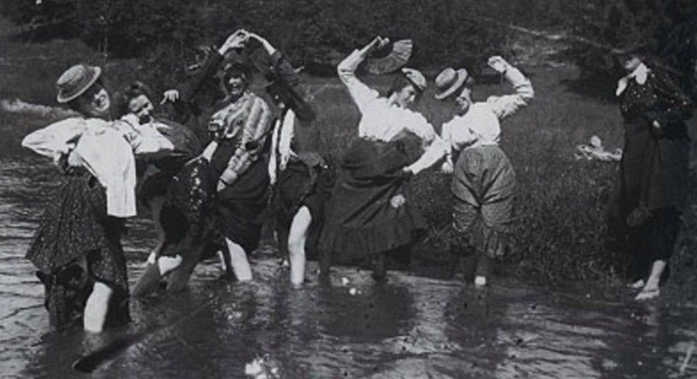 women with their skirts tucked up wading in a stream