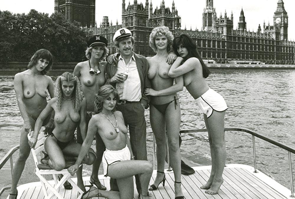 Paul Raymond with topless nude dancers on the deck of a fancy yacht in the Thames in London England